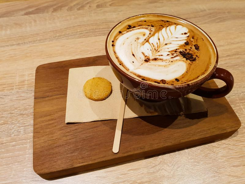 Hot Coffee Macchiato Latte Art serving with cookie royalty free stock images
