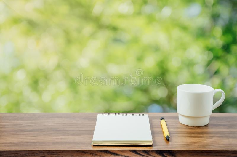 Hot coffee, , notebook and pen in nature background royalty free stock photography