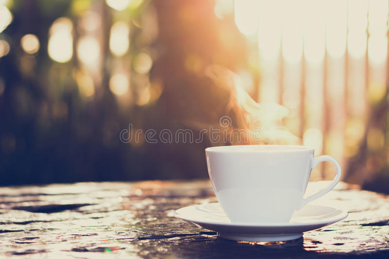 Hot coffee on old wood table with blur background of sunlight shining through the trees royalty free stock photography