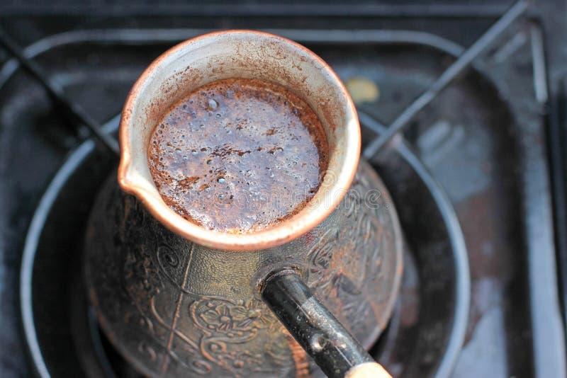 Hot coffee prepared in turk on gas. Closeup.  royalty free stock photos