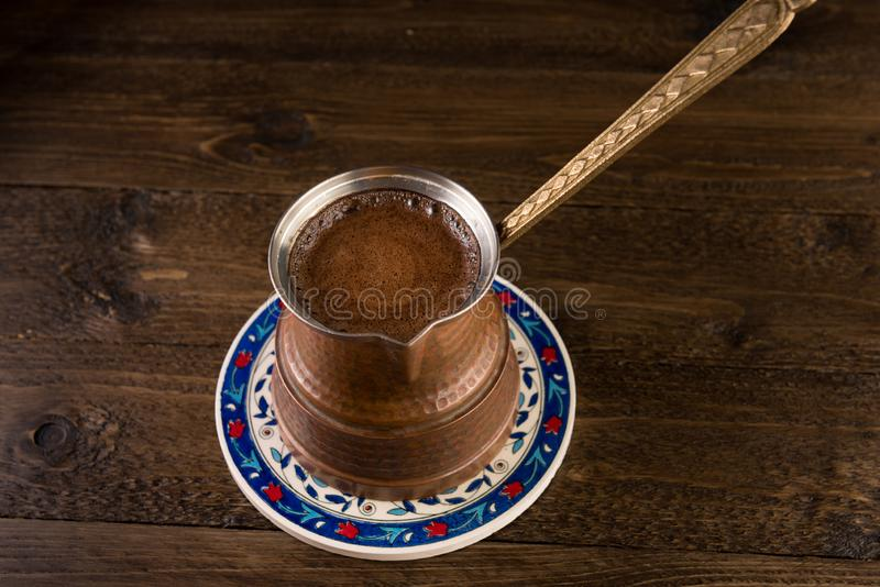 Hot coffee prepared in a Turk. View on a beautiful wooden table royalty free stock photos