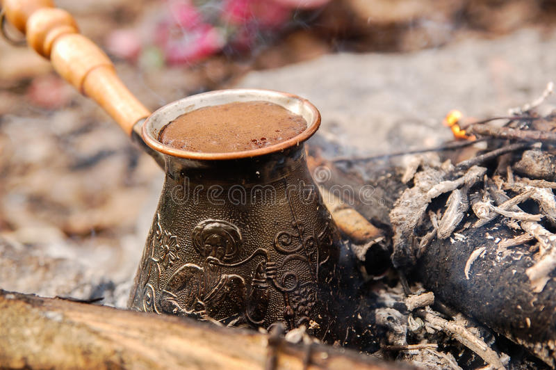 Hot coffee prepared in turk on open fire. Closeup. Hot coffee prepared in turk on open fire. Closeup stock photography