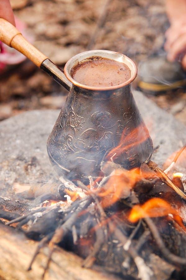 Hot coffee prepared in turk on open fire. Closeup.  stock photo
