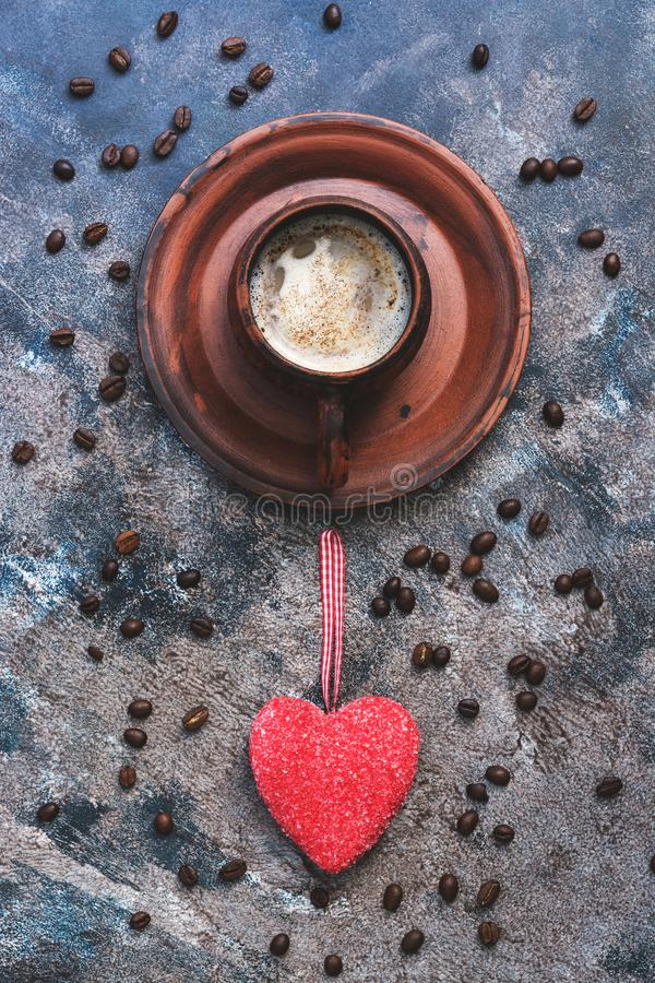 Hot coffee and red heart on a rustic abstract background. The concept of celebration, the day of lovers. View from above stock photos