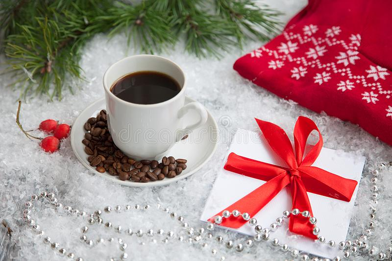 hot coffee, red warm pullover and gift with a red bow on a snowy background royalty free stock photos