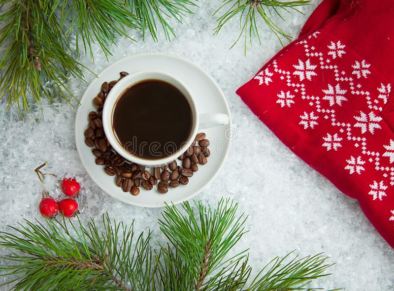 Hot coffee, red warm pullover and gift with a red bow on a snowy background royalty free stock photo