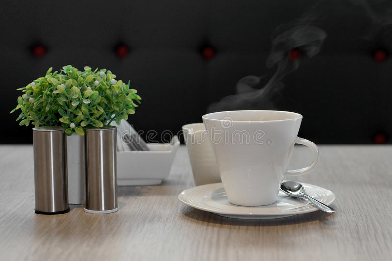 Hot coffee with steam. Cup of hot coffee with steam on wooden table stock images