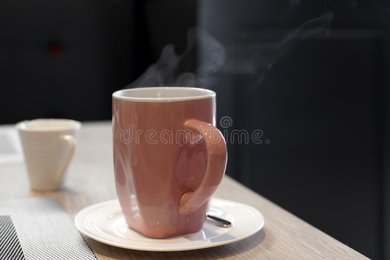 Hot coffee with steam. Cup of hot coffee with steam on wooden table royalty free stock image
