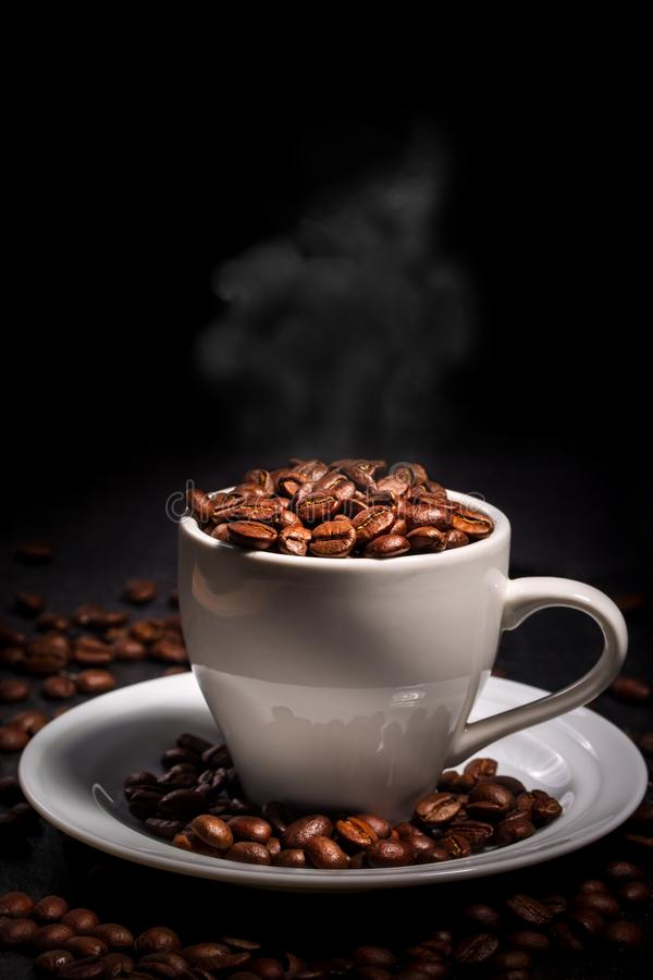 Hot coffee with steam. White cup with coffee grains on a black background stock images