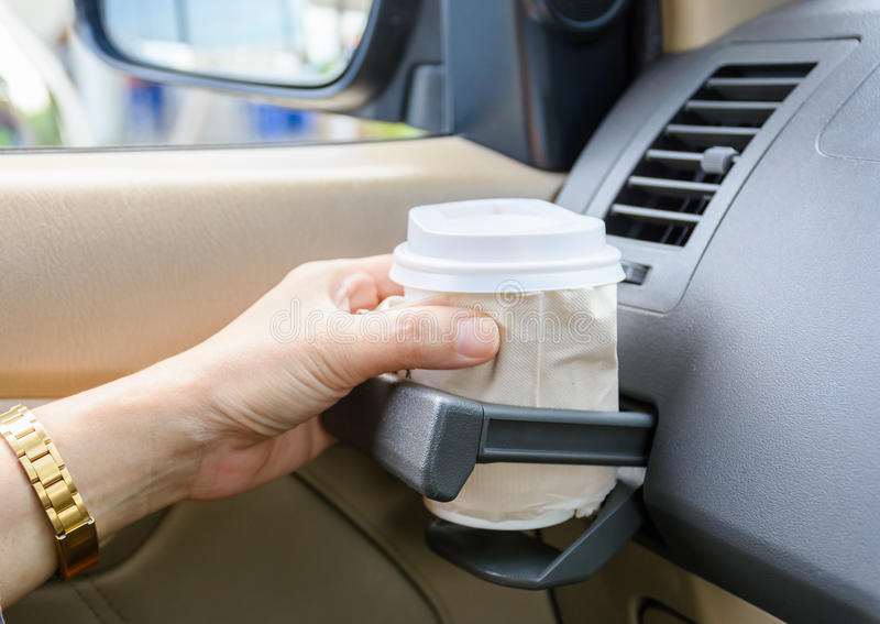 Hot coffee to go at cup holder in a car. royalty free stock image