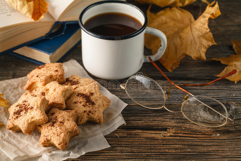 Hot coffee, vintage book, glasses and autumn leaves on wood back stock photos