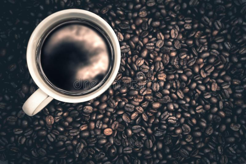Hot coffee is in a white cup Put on wooden floor With coffee beans royalty free stock photography