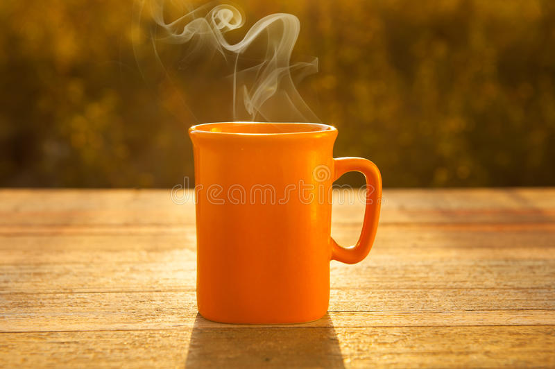 Hot coffee on wood table in sunset royalty free stock photo