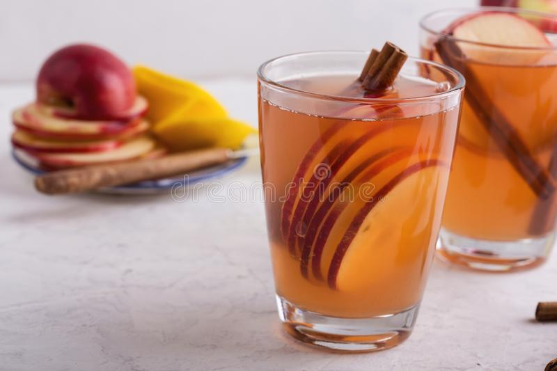 Hot cozy autumn and winter mulled cider drinks with apple slices. In glass mugs royalty free stock image