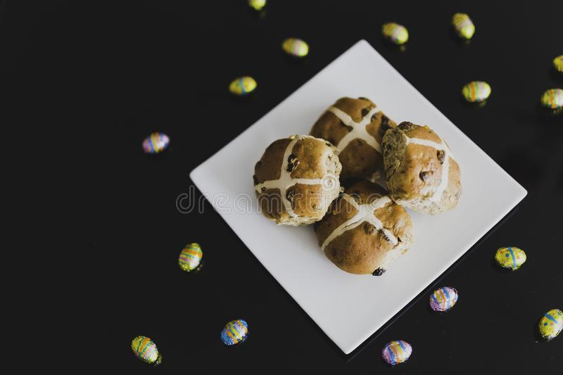 Hot cross buns on black table with chocolate eggs around royalty free stock photo