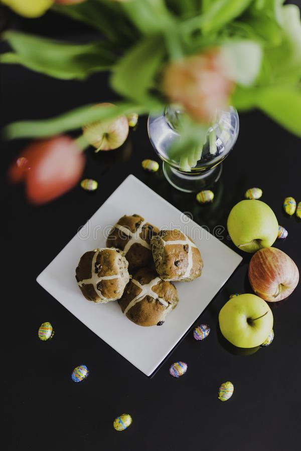 Easter hot cross buns and chocolate eggs with apples and flowers stock photos
