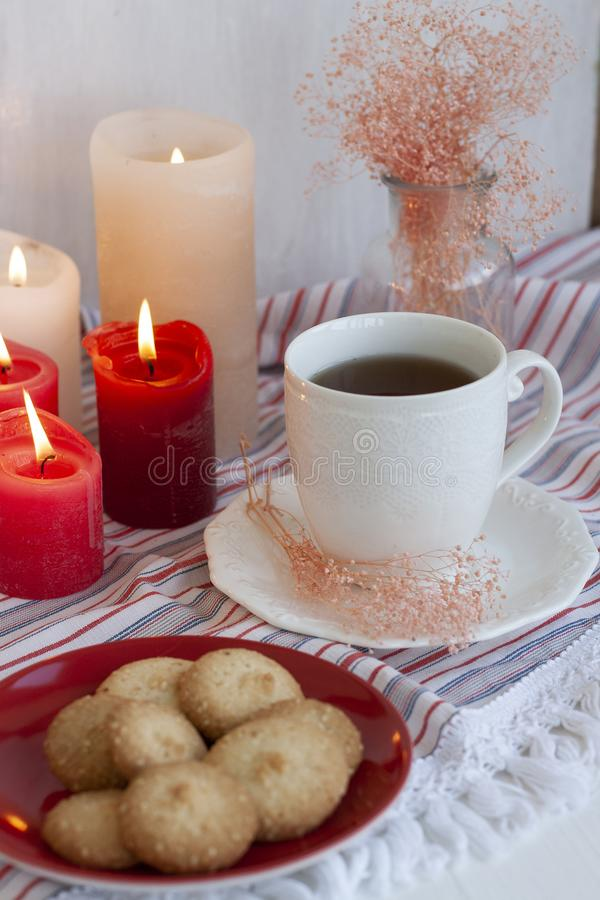 A hot cup of black tea with homemade cookies on a striped tablecloth, wax candles, a glass vase with decorative herbs on a white royalty free stock photo