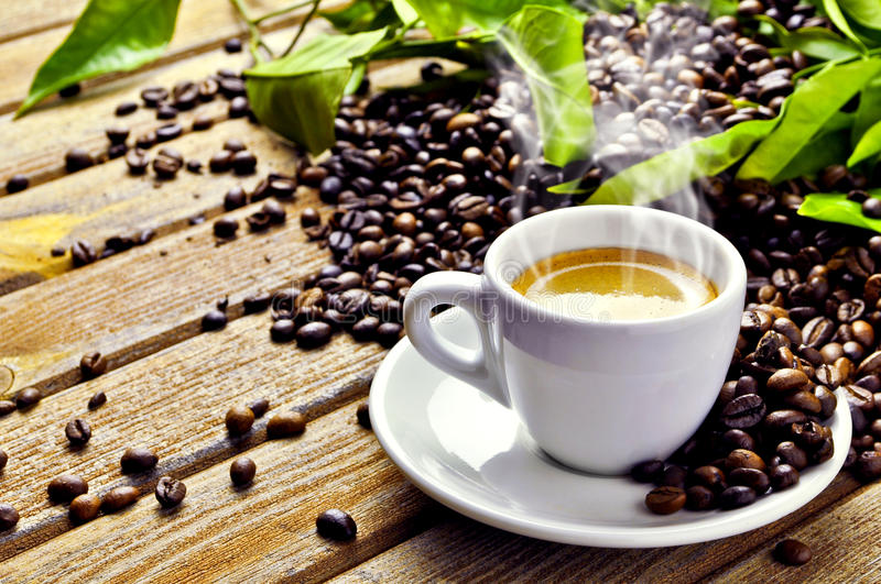 Hot Cup of coffee. A hot cup of coffee with coffee-beans and green leaves royalty free stock photography