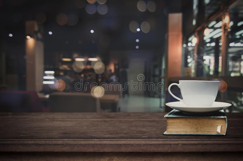 Hot cup of coffee on big book on wood table in front of blurred royalty free stock photo
