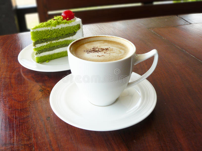Hot cup of coffee cappuccino and layer green tea cake. Decorated with red cherry in white plate on wooden table stock photos