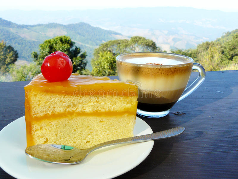 Hot cup of coffee and orange cake. Hot cup of coffee, the layer of cappuccino in transparent glass with tea spoon and orange cake decorated with red cherry in stock photos