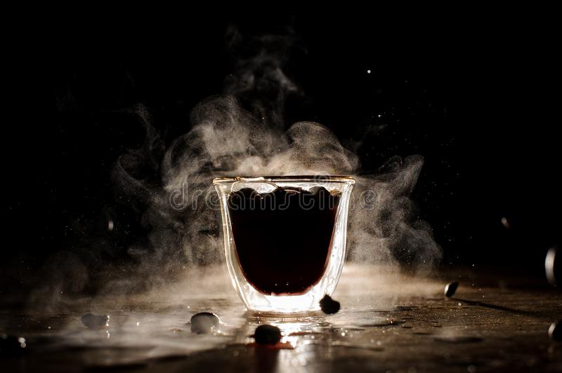 Hot cup of coffee with steam located on the table. Splashes of coffee from hot mug located on the wooden table on the black background royalty free stock photography
