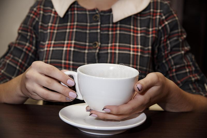 Hot cup with drink in female hands stock photos