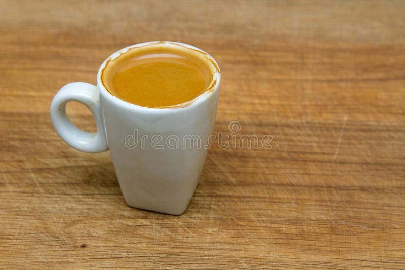 Hot cup of espresso on a wooden background. Top view of coffee in plate with spoon put on white wooden tabletop and sunlight royalty free stock photo