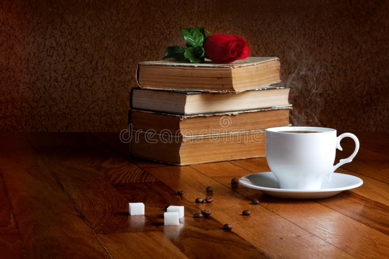 Hot cup of fresh coffee on the wooden table. And stack of books to read with red rose royalty free stock photography