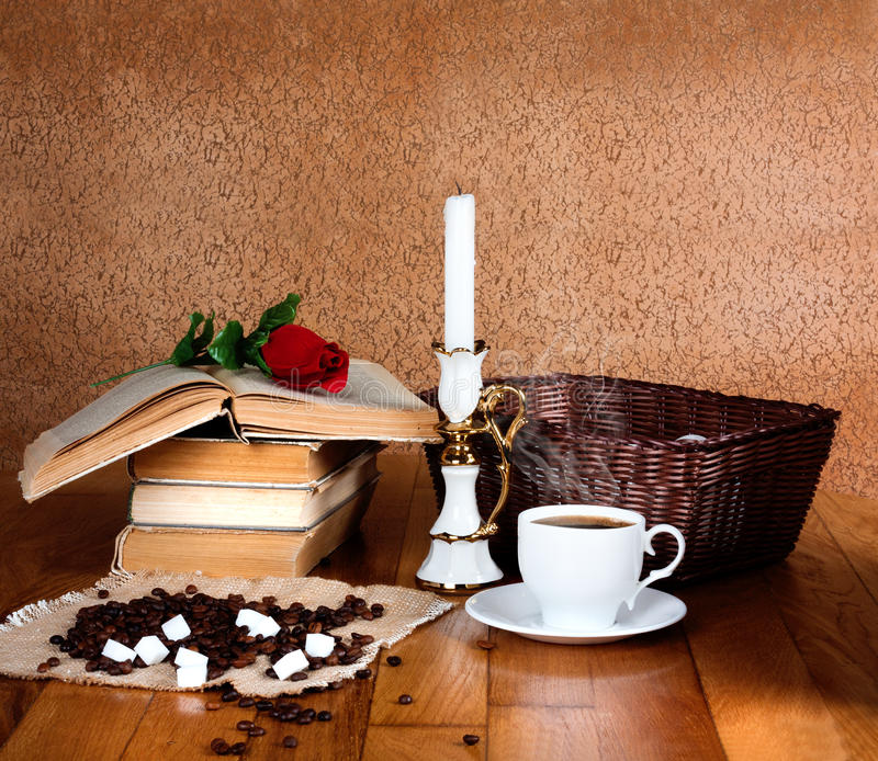 Hot cup of fresh coffee on the wooden table. And stack of books to read with red rose stock photo