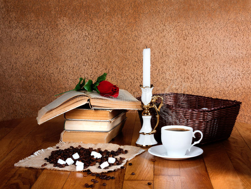 Hot cup of fresh coffee on the wooden table. And stack of books to read with red rose royalty free stock photo