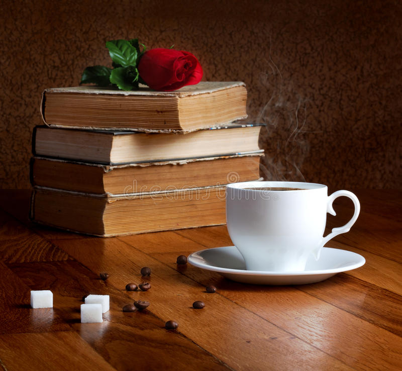 Hot cup of fresh coffee on the wooden table. And stack of books to read with red rose stock images