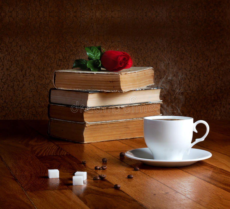 Hot cup of fresh coffee on the wooden table. And stack of books to read with red rose royalty free stock image