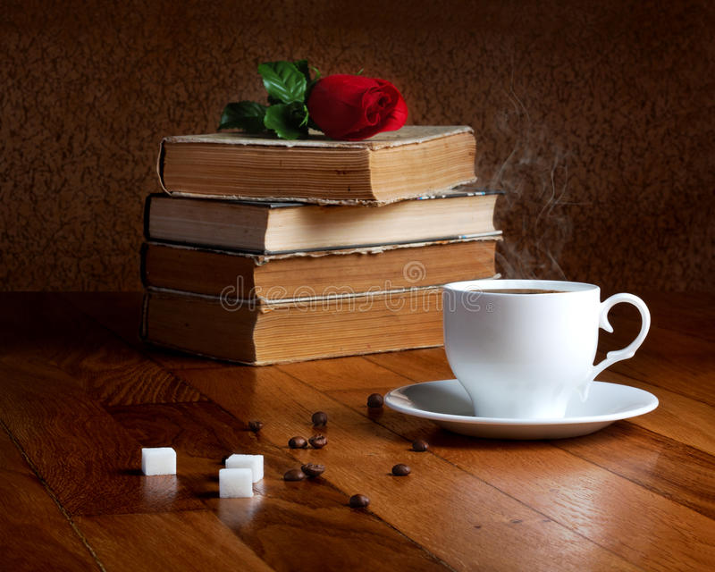 Hot cup of fresh coffee on the wooden table. And stack of books to read with red rose stock photos