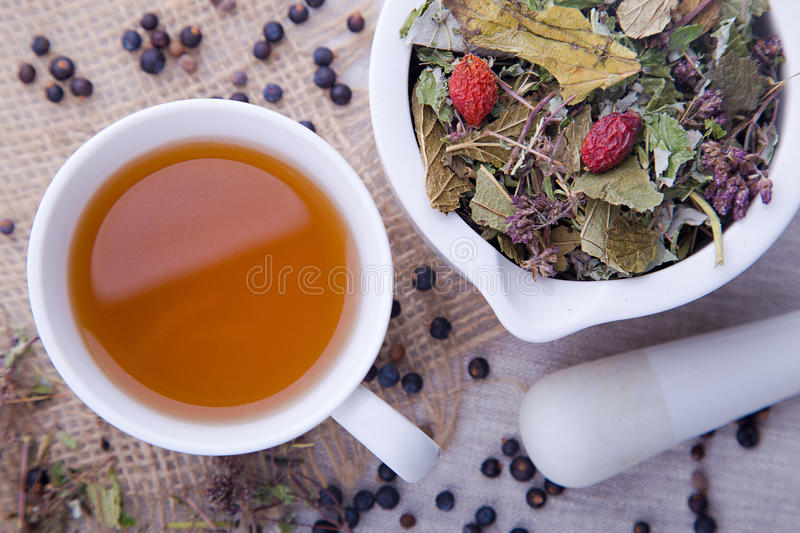 Hot cup of herbal and blackberry tea with white mortar with pestle royalty free stock photo