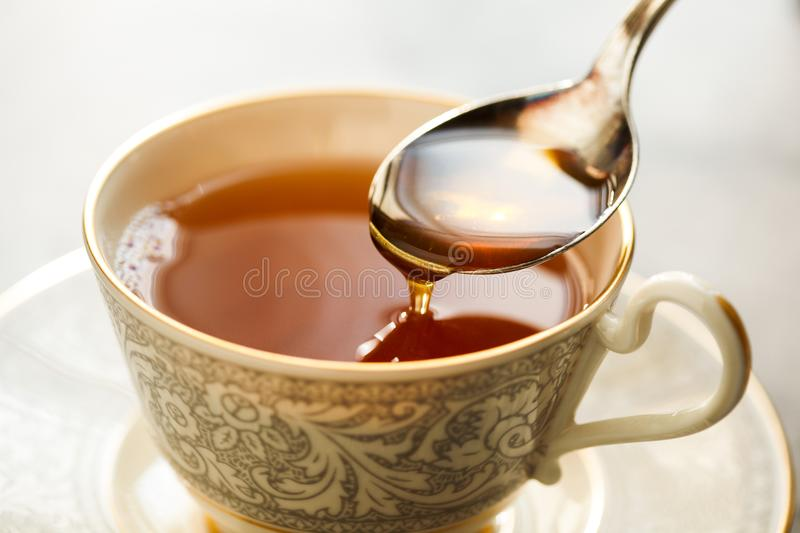 A Spoonful of Honey About to Drop into Tea. A hot cup of tea awaiting a spoonful of local honey royalty free stock photography
