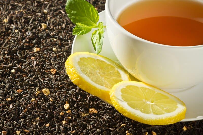 Hot cup of tea with lemon on grain stock photo