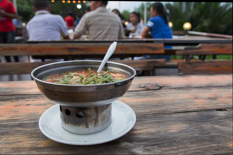 Hot Curry orange soup with fish and Mesmerize vegetable. Thai food menu in iron pot for dinner party. a famous Thai food, good heat food from herb vegetable stock photo