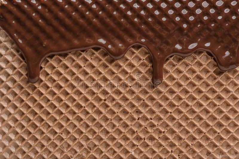 Hot dark chocolate on wafer, closeup. Crispy food royalty free stock photography