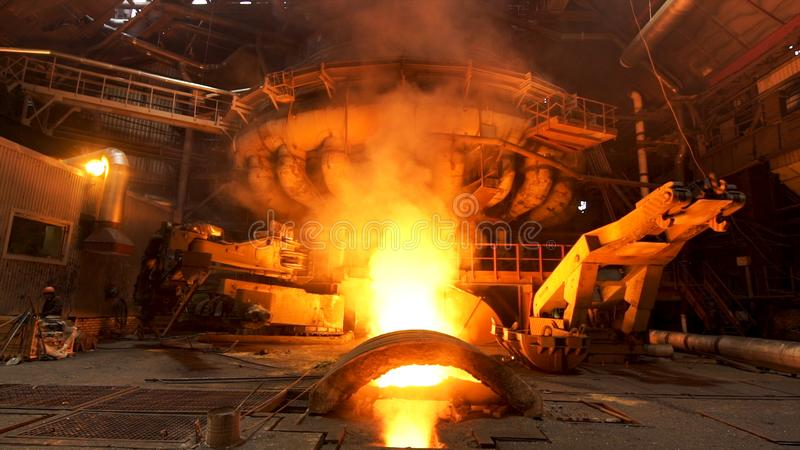Hot dark workshop of steel production in electric furnaces, with burning fire and smoke. Stock footage. Metallurgical stock photo