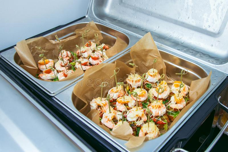 Hot Delicates, appetizer canape with tiger shrimp, fused cheese and vegetables. Catering service. royalty free stock image