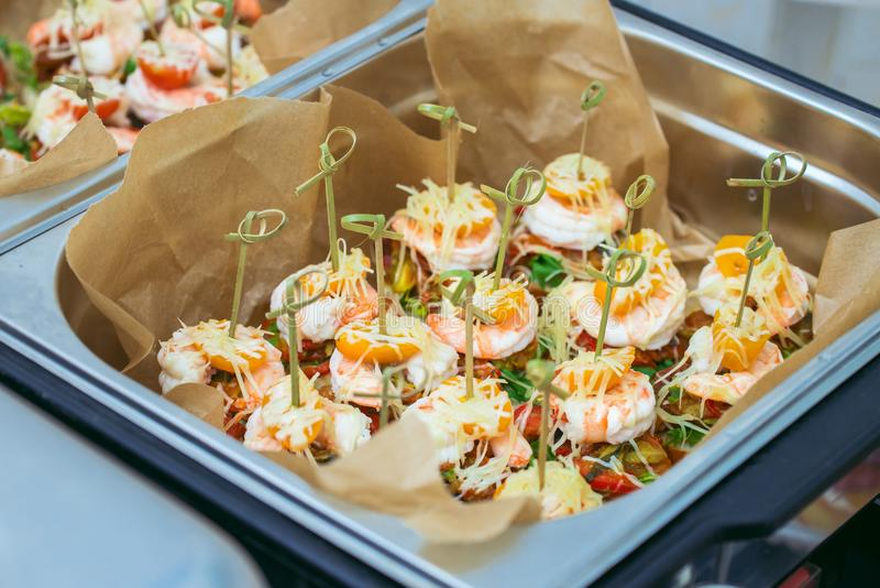 Hot Delicates, appetizer canape with tiger shrimp, fused cheese and vegetables. Catering service. stock photos