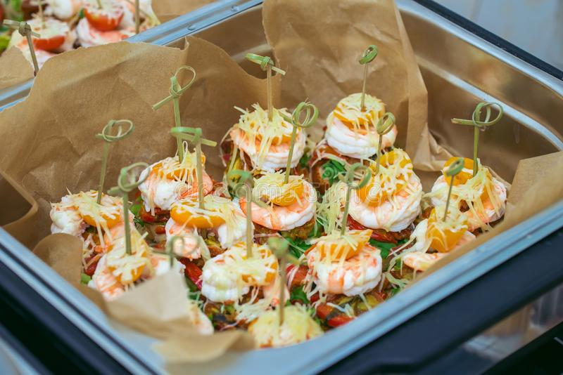 Hot Delicates, appetizer canape with tiger shrimp, fused cheese and vegetables. Catering service. royalty free stock photos