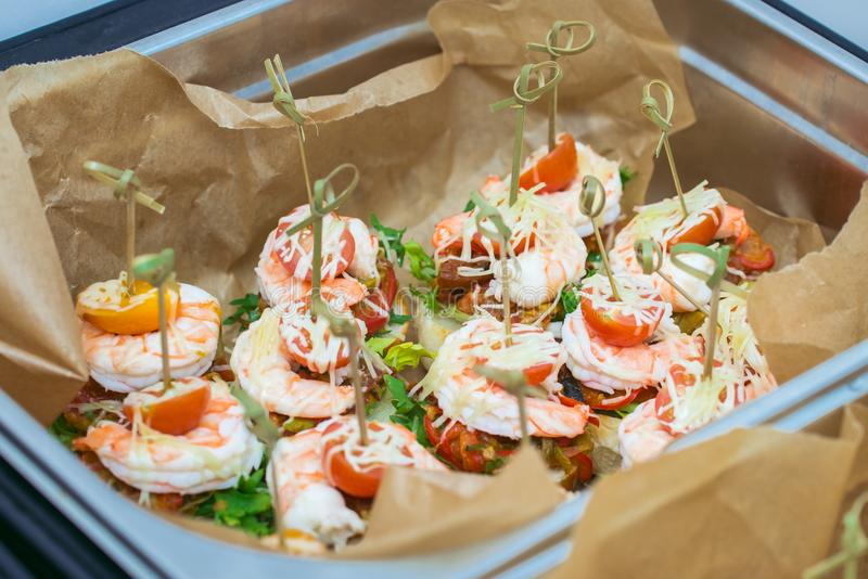Hot Delicates, appetizer canape with tiger shrimp, fused cheese and vegetables. Catering service. stock images