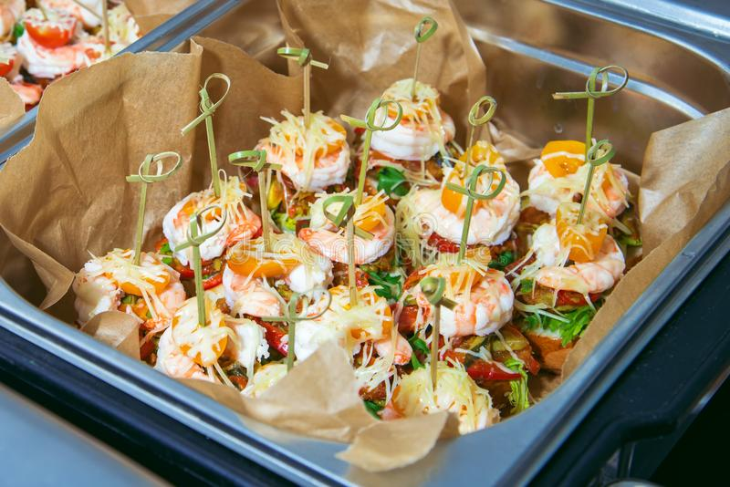 Hot Delicates, appetizer canape with tiger shrimp, fused cheese and vegetables. Catering service. royalty free stock photo