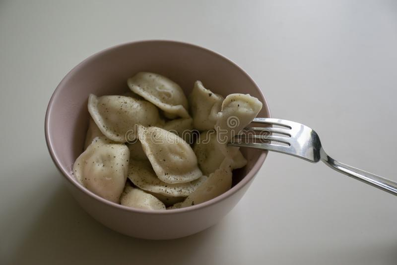 Hot dumplings with pepper on them in pink plate on white table with silver fork. Hot delicios dumplings with pepper on them in pink plate on white table with royalty free stock photo