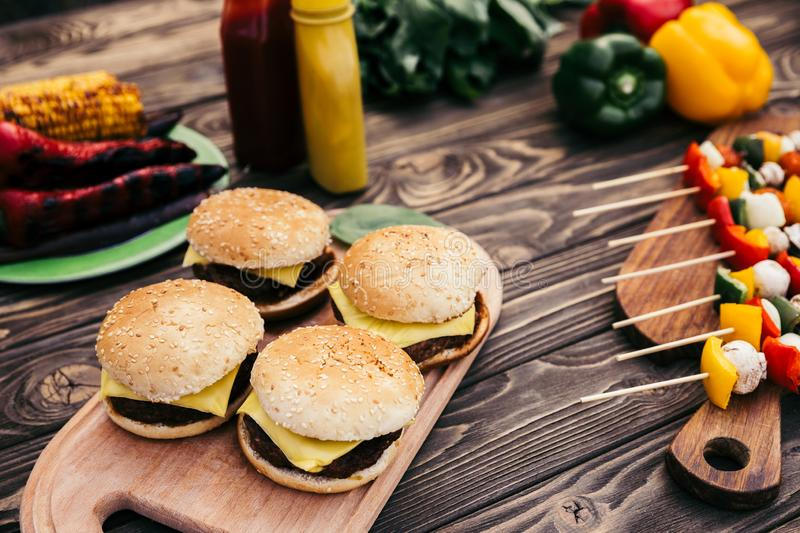 Hot delicious burgers and vegetables grilled for outdoors barbecue royalty free stock photo