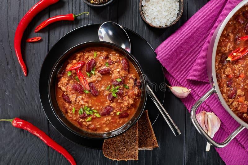 Chili con carne in black bowl stock image