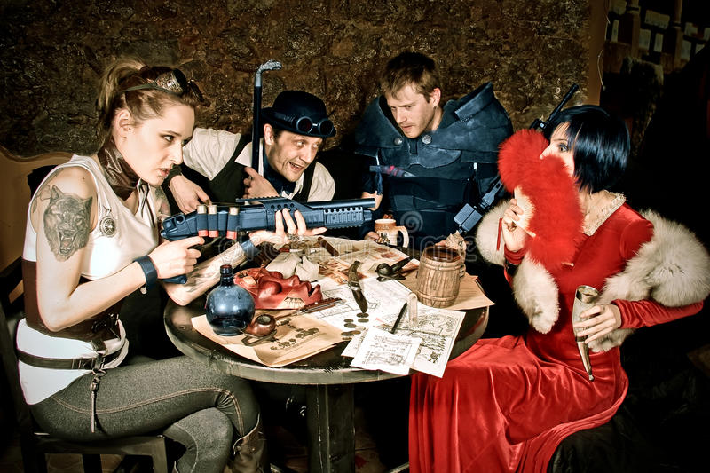 Hot discussion. A team of adventurers is disputing at the taverns table royalty free stock photography