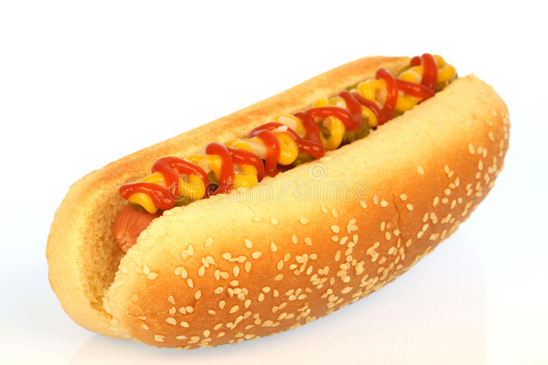 Hot dog. Against white background with onions, pickles,ketchup and mustard on top royalty free stock photography
